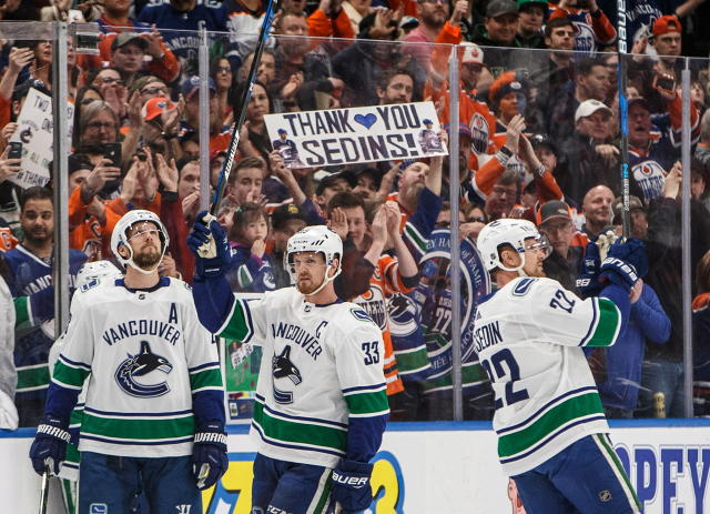 Vancouver Canucks' Henrik Sedin (33) and Daniel Sedin (22) acknowledge the crowd as it cheers for them during a break against the Edmonton Oilers in Edmonton, Alberta, Saturday, April 7, 2018. (Jason Franson/The Canadian Press via AP)