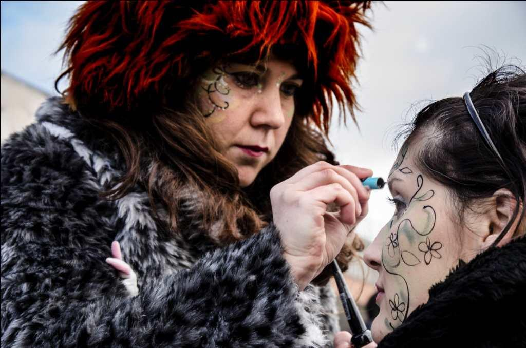 Revellers paint faces for the Carnival.