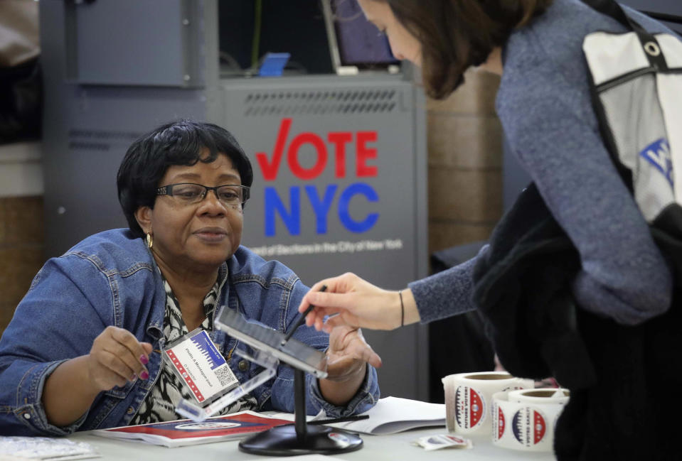 FILE - In this Oct. 26, 2019, file photo, a polling site inspector processes a voter using the new E-Poll Book tablet, during early voting at Brooklyn's Clara Barton High School in New York. Electronic poll books are computer software used in polling places on Election Day. The software allows election inspectors to look up a voter's registration record, confirm the registration is correct and assign a ballot to that voter. (AP Photo/Bebeto Matthews, File)