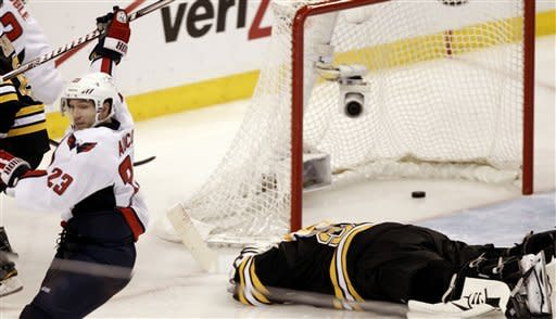 Washington Capitals' Keith Aucoin (23) celebrates a goal by teammate Mike Knuble as Boston Bruins goalie Tim Thomas lies face down on the ice during the third period of Washington's 4-3 win in Game 5 in a first-round NHL Stanley Cup playoff hockey series in Boston Saturday, April 21, 2012. (AP Photo/Winslow Townson)