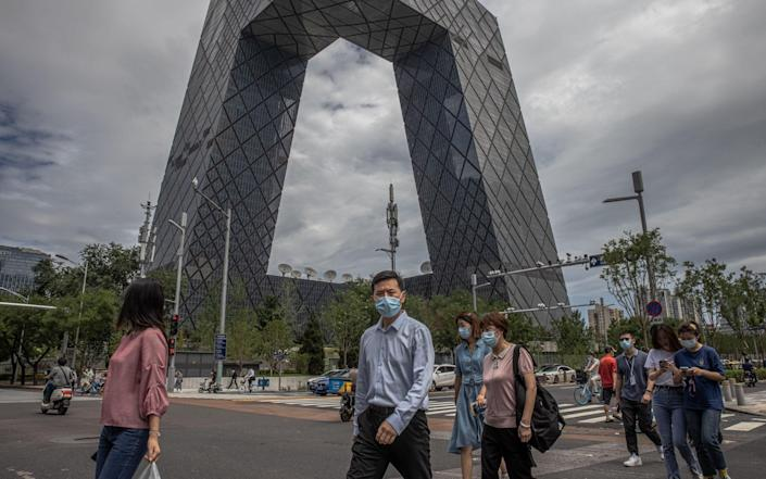 People wearing face masks cross the road in the Central Business District (CBD) area of Beijing, - ROMAN PILIPEY/Shutterstock