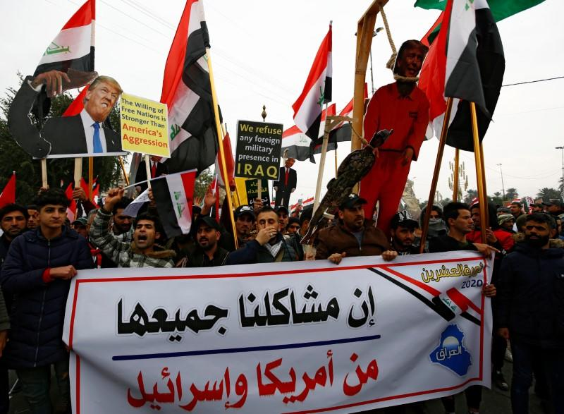 """Supporters of Iraqi Shi'ite cleric Moqtada al-Sadr hold a sign reading """"Our problems are all from America and Israel"""" at a protest against what they say is U.S. presence and violations in Iraq, in Baghdad"""