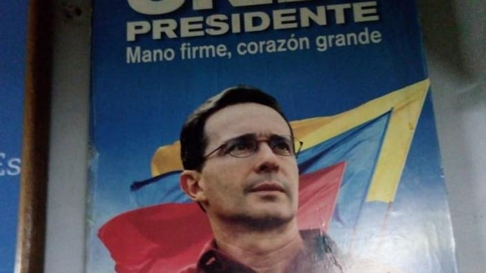 Old campaign posters of Álvaro Uribe line the walls of Mr Alzate's home
