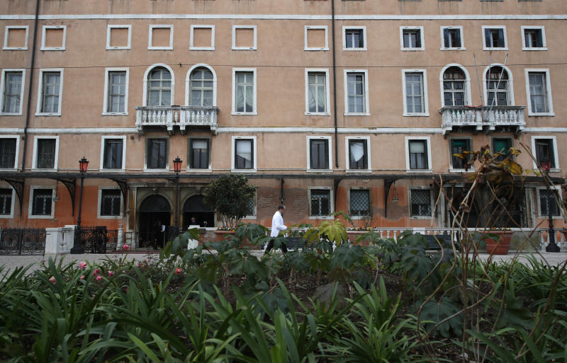 A waiter walks at the newly restored Royal Gardens in Venice, Italy, Tuesday, Dec. 17, 2019. Venice's Royal Gardens were first envisioned by Napolean, flourished under Austrian Empress Sisi and were finally opened to the public by the Court of Savoy, until falling into disrepair in recent years. After an extensive restoration, the gardens reopened Tuesday as a symbol both of the lagoon city's endurance and the necessity of public-private partnerships to care for Italy's extensive cultural heritage. (AP Photo/Antonio Calanni)