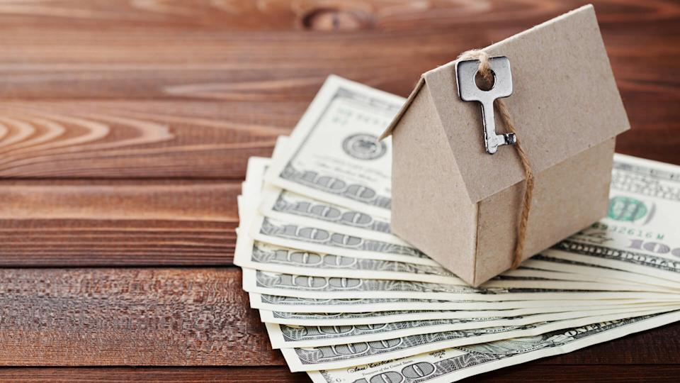 Model of cardboard house with key and dollar money.