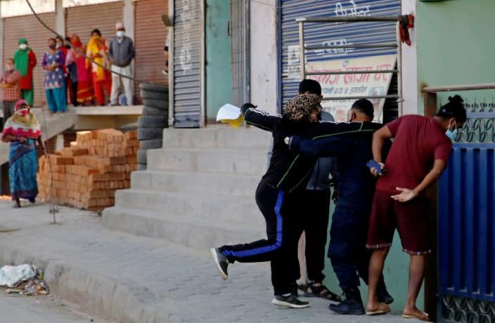 A local protester punches a man during an argument about Indonesians taking shelter at the mosque, amid fear of outsiders spreading coronavirus disease (COVID-19), at Jame Masjid in Imadol, Lalitpur