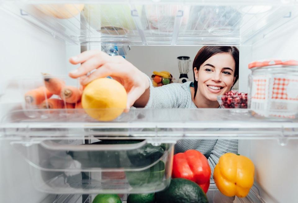 woman reaches for food in the fridge