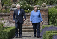 Britain's Prime Minister Boris Johnson, left, and German Chancellor Angela Merkel, walk through the garden at Chequers, the country house of the Prime Minister, in Buckinghamshire, England, Friday July 2, 2021. Johnson is likely to push Angela Merkel to drop her efforts to impose COVID-19 restrictions on British travelers as the German chancellor makes her final visit to Britain before stepping down in the coming months. Johnson will hold talks with Merkel at his country residence on Friday. (David Rose/Pool Photo via AP)