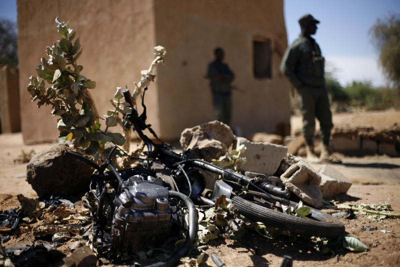 Malian soldiers stand by the remains of a motorcycle used by a suicide bomber at the entrance of Gao, northern Mali, Friday Feb. 8, 2013, It was the first known time a suicide bomber operated in Mali. (AP Photo/Jerome Delay)