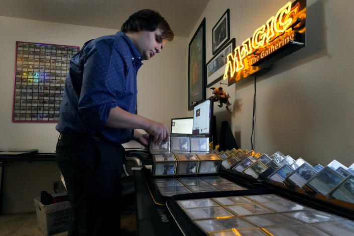 Austin Deceder sorts Magic cards in his home office Friday, Aug. 27, 2021, in Kansas City, Mo. Prices of the collectable cards and vintage video games that Deceder and others buy and sell have skyrocketed in the past few months to the dismay of hobbyists. (AP Photo/Charlie Riedel)