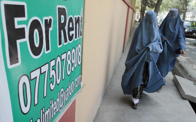 In this Monday, July 16, 2012 photo Afghan women walk past a house rental sign in Kabul, Afghanistan. Donor nations have pledged to keep bankrolling the Afghan security forces and send more development money, but none of this has done much to raise the hopes of many Afghans who remain in deep despair about the future of their nation after international troops leave. (AP Photo/Musadeq Sadeq)