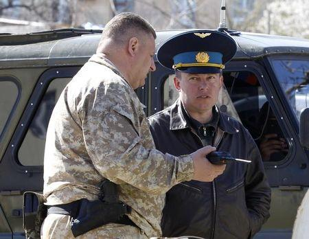 A Russian military officer (L) talks to Ukrainian Colonel Yuli Mamchur (L), demanding Ukrainian servicemen leave a military base in the Crimean town of Belbek near Sevastopol March 22, 2014. REUTERS/Vasily Fedosenko/Files