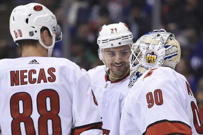 Carolina Hurricanes right wing Nino Niederreiter (21) and center Martin Necas (88) speak to Hurricanes emergency goalie David Ayres as he takes the ice against the Toronto Maple Leafs during second-period NHL hockey game action in Toronto, Saturday, Feb. 22, 2020. (Frank Gunn/The Canadian Press via AP)
