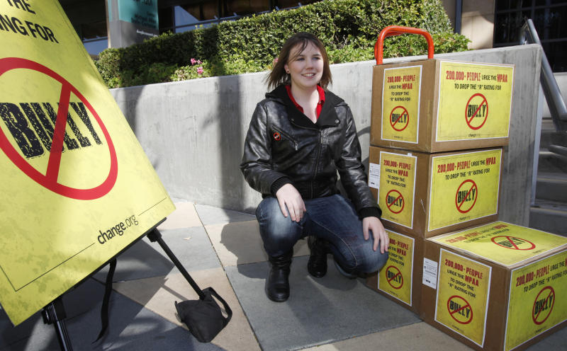 """Katy Butler, 17, a high school student, from Ann Arbor, Mich., poses by the petitions she delivered to the Motion Picture Association of America, Wednesday March 7, 2012, in Los Angeles. Butler is urging the MPAA  to change the """"R"""" rating to a """"PG"""" for the """"Bully"""" film. With her petition, Butler said that she was speaking out for all students who suffer every day from bullying. (AP Photo/Damian Dovarganes)"""