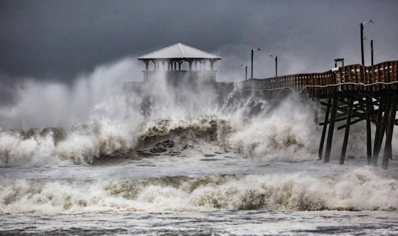 <p>Das ausgedehnte Windfeld des Hurrikans bringt hohe Wellen mit sich, die jeden Tag hoher und stärker werden, wie hier am Oceanana Pier & Pier House Restaurant in Atlantic Beach, North Carolina. (Bild: Travis Long/The News & Observer via AP Photo) </p>