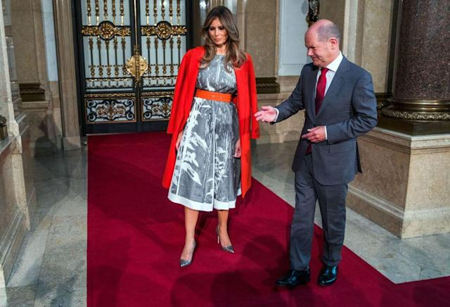 """<p>For a final appearance at the G20 summit, Melania Trump wore a grey and white Herve Pierre dress (Pierre designed her inauguration gown), a red Bottega Veneta coat that <a href=""""http://www.neimanmarcus.com/Bottega-Veneta-Double-Cashmere-Wrap-Coat/prod189410180/p.prod?ecid=NMCS__GooglePLA&utm_medium=CSE&utm_source=NMCS__GooglePLA&utm_campaign=BottegaVeneta&ecid=NMAF__Skimlinks.com&CS_003=5630585&utm_medium=affiliate&utm_source=NMAF__Skimlinks.com"""" rel=""""nofollow noopener"""" target=""""_blank"""" data-ylk=""""slk:retails"""" class=""""link rapid-noclick-resp"""">retails</a> for $5,400, and silver snakeskin Manolo Blahniks.</p>"""