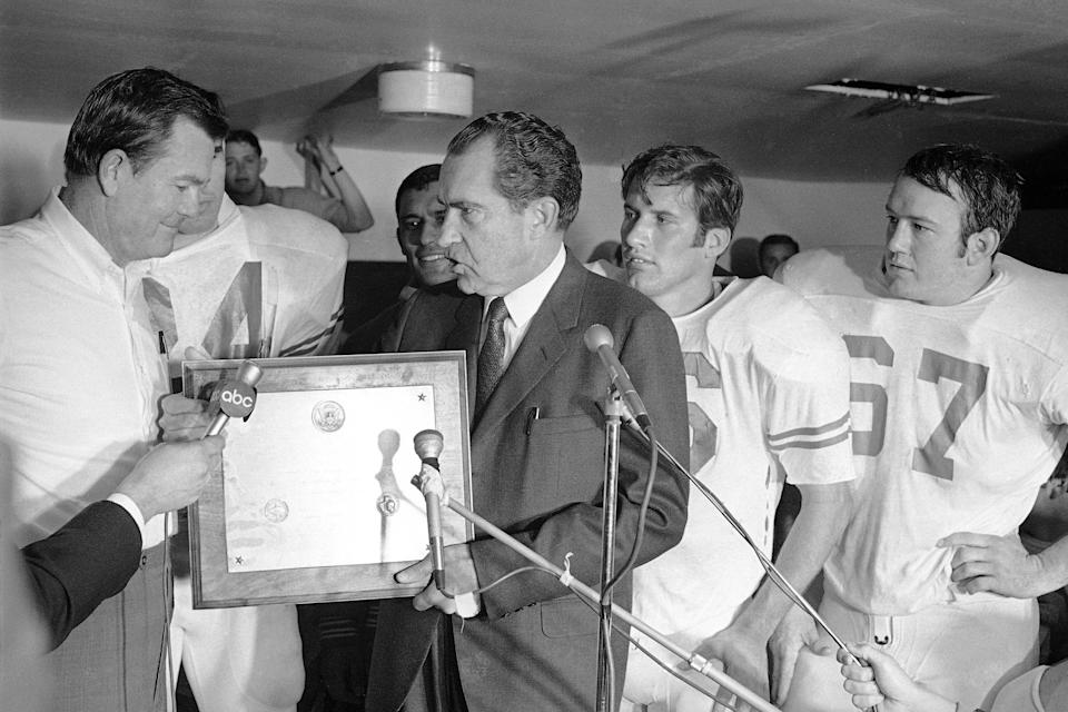 FILE - In this Dec. 6, 1969, file photo, President Richard Nixon presents a plaque to Texas football coach Darrell Royal, naming the Longhorns the No. 1 college football team in college football as linebacker Glen Halsell (67) and quarterback James Street (16) watch. The Longhorns' fourth-quarter comeback led by Street erased Arkansas' 14-0 lead and sent Texas unbeaten into the Cotton Bowl, but it wasn't even the memorable part of the event for many who remember it. Nixon arrived by helicopter to attend the game, and after he declared the Longhorns national champions —- before they even played their bowl game. (AP Photo/File)