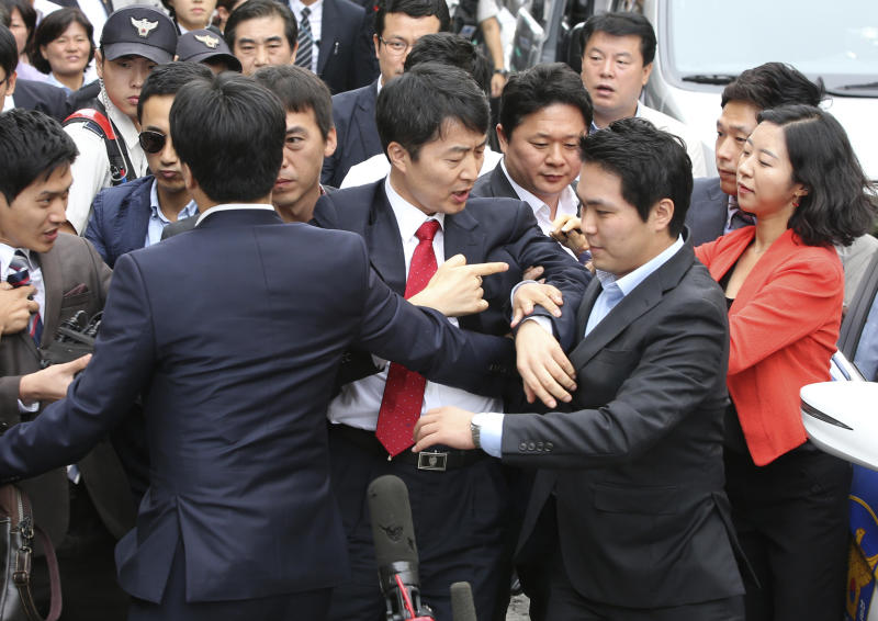 South Korean lawmaker Lee Seok-ki, center, of the leftist Unified Progressive Party arrives at the Suwon District Court in Suwon in Suwon, south of Seoul, Thursday, Sept. 5, 2013. South Korea's spy agency on Thursday arrested Lee implicated in an allegation of rebellion that has sparked a political firestorm in the country which faces a persistent threat from rival North Korea. The arrest of Lee was made after the court issued a warrant for his detention following hours of review. A day earlier, the country's parliament voted to remove Lee's legislative immunity against his arrest in their first passage of such a motion over rebellion charges. (AP Photo/Yonhap, Kim Ju-sung) KOREA OUT
