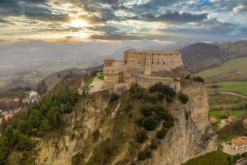 Aerial view of San Leo town and fortress used once as a prison on a rocky outcrop near the Adriatic sea resort Rimini and San Marino with Roman church