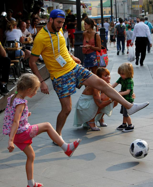 A Brazil fan plays with a ball with children as he celebrates Brazil's victory over Costa Rica at the World Cup Group E soccer match in central Moscow, Russia June 22, 2018. REUTERS/Sergei Karpukhin