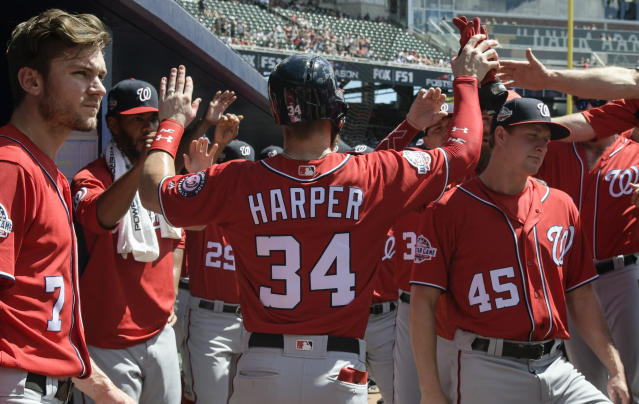 Washington Nationals' Bryce Harper is congratulated in the dugout after scoring on Juan Soto's RBI single in the first inning of a baseball game against the Atlanta Braves, Saturday, Sept. 15, 2018, in Atlanta. (AP Photo/John Amis)
