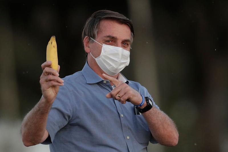 El presidente de Brasil, Jair Bolsonaro, con mascarilla y un plátano el 24 de julio de 2020 (AP Photo/Eraldo Peres). (Photo: ASSOCIATED PRESS)