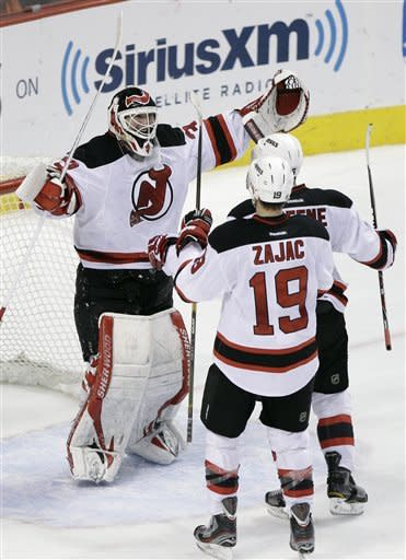 New Jersey Devils' Martin Brodeur, Travis Zajac and Andy Greene. from left, celebrate after the Devils won Game 5 of a second-round NHL hockey Stanley Cup playoff series against the Philadelphia Flyers, Tuesday, May 8, 2012, in Philadelphia. New Jersey won 3-1 and won the series 4-1. (AP Photo/Matt Slocum)
