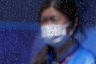 A masked worker walks by a rain-covered window after a rain storm at a field hockey match at the 2020 Summer Olympics, Tuesday, July 27, 2021, in Tokyo, Japan. (AP Photo/John Locher)