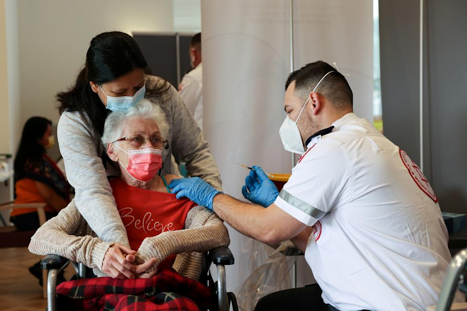 A elderly woman receives a booster shot