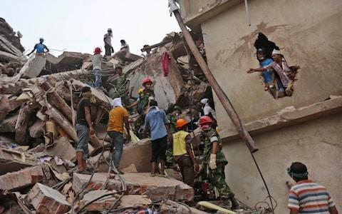 Bangladeshi rescue workers search for victims amid the rubble of a collapsed building in Savar, near Dhaka, Bangladesh - Credit: AP