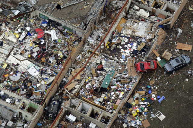 An aerial view shows Briarwood Elementary with vehicles thrown about after Monday's tornado, Tuesday, May 21, 2013, in Moore, Okla. At least 24 people, including nine children, were killed in the massive tornado that flattened homes and a school in Moore, on Monday afternoon. (AP Photo/Tony Gutierrez)