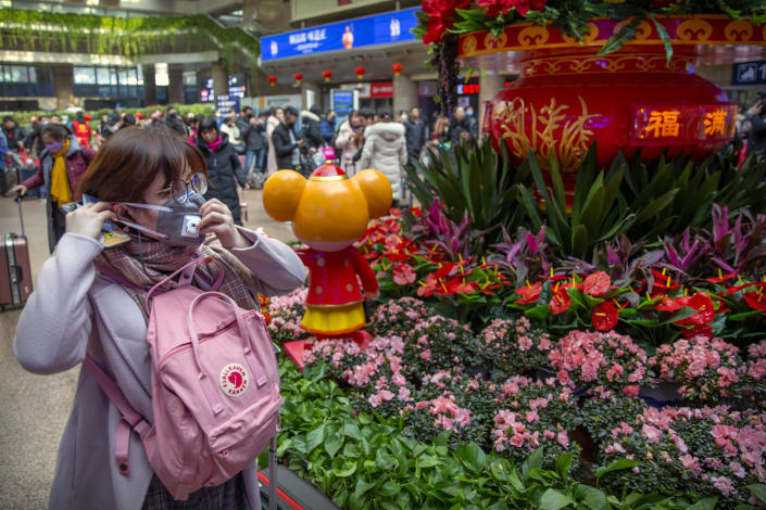 A traveler adjusts her face mask next to a display for the upcoming Lunar New Year at the Beijing West Railway Station in Beijing, Tuesday, Jan. 21, 2020. A fourth person has died in an outbreak of a new coronavirus in China, authorities said Tuesday, as more places stepped up medical screening of travelers from the country as it enters its busiest travel period. (AP Photo/Mark Schiefelbein)