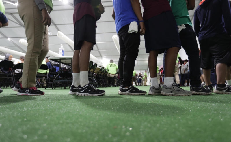 FILE - In this July 9, 2019, file photo, immigrants line up in the dinning hall at the U.S. government's newest holding center for migrant children in Carrizo Springs, Texas. The government will be able to hold immigrant children detained at the Mexican border for a longer period of time under a move by the Trump administration (AP Photo/Eric Gay, File)