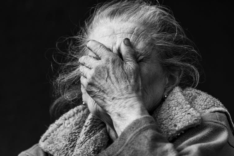 Black and white image of old lady in distress covering her face with her hand.