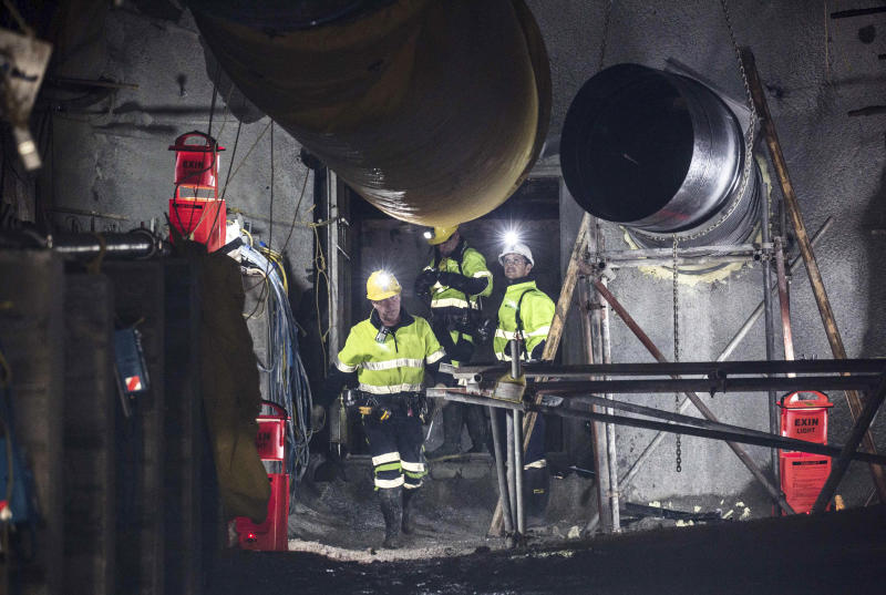 In this image released by the Pike River Recovery Agency, workers react after the first of the two airlock doors was opened in the Pike River Mine, near Greymouth on the West Coast of New Zealand, Tuesday, May 21, 2019. Crews in New Zealand on Tuesday reentered an underground coal mine where a methane explosion killed 29 workers more than eight years ago, raising hopes among family members that they might find bodies and new evidence that leads to criminal charges. (Neil Silverwood/Pike River Recovery Agency via AP)