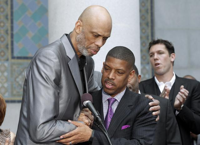 Sacramento, Calif., Mayor Kevin Johnson, center, and Hall of Famer Kareem Abdul-Jabbar embrace during a news conference outside City Hall in Los Angeles Tuesday, April 29, 2014, after Johnson's comments on the decision by NBA commissioner Adam Silver to ban Los Angeles Clippers owner Donald Sterling from basketball for life in response to racist comments the league says Sterling made in a recorded conversation. Former NBA player Luke Walton applauds at rear right rear. (AP Photo)