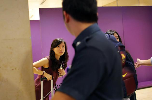 The fiancée of Alain Oktavianus Siaun, one of the 162 people on board AirAsia flight QZ8501, arrives at the relatives holding area in Changi Airport on Sunday, 28 December 2014. (Associated Press photo)