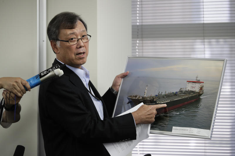 Yutaka Katada, president of Kokuka Sangyo Co., the Japanese company operating one of two oil tankers attacked near the Strait of Hormuz, shows a photo of the attacked oil tanker during a news conference Friday, June 14, 2019, in Tokyo. Iran rejects a U.S. accusation against Tehran over suspected attacks on two oil tankers near the strategic Strait of Hormuz. (AP Photo/Jae C. Hong)