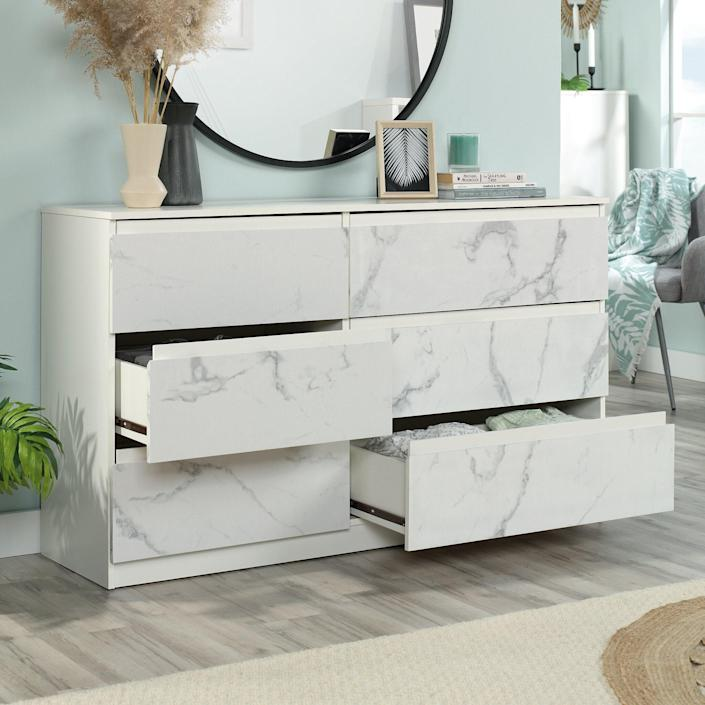 """Detailed with chamfered edge fronts and accented with faux marble, this luxe-looking piece from Wayfair was designed with smart storage in mind: three small drawers and three large ones that open and close on smooth runners. This fun dresser is style and function at its best. $340, Wayfair. <a href=""""https://www.wayfair.com/furniture/pdp/latitude-run-amy-jayne-6-drawer-dresser-w003213095.html?"""" rel=""""nofollow noopener"""" target=""""_blank"""" data-ylk=""""slk:Get it now!"""" class=""""link rapid-noclick-resp"""">Get it now!</a>"""