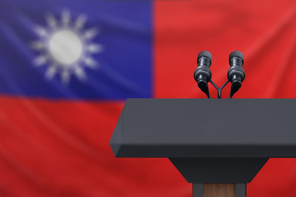 Podium lectern with two microphones and Taiwan flag in background
