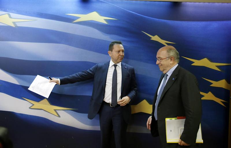 """Greece's Finance Minister Yannis Stournaras, left, arrives for a news conference with European Union's Vice President and Competition Commissioner Joaquin Almunia in Athens on Thursday, April 10, 2014. Buoyant Greek officials said the government had received strong interest for its first bond issue in four years, with Thursday's auction of five-year debt being about eight times oversubscribed — a sign of growing market confidence. """"Greece has succeeded — and this is recognized by our most critical friends and partners — in achieving an exit from the crisis, or is very close to an exit from the crisis,"""" Stournaras said on Thursday. (AP Photo/Thanassis Stavrakis)"""