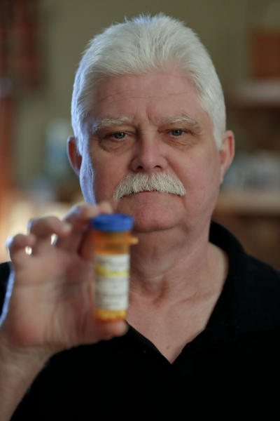 In this April 8, 2019, photo at his home in Derry, Pa., Chuck Pope shows the only medication he uses now to alleviate his rheumatoid arthritis condition. (AP Photo/Keith Srakocic)