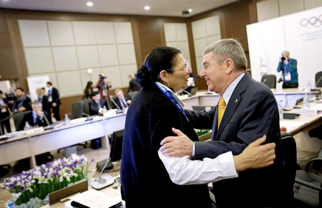 FILE - In this Sunday, Feb. 2, 2014, file photo, International Olympic Committee President Thomas Bach, right, embraces executive board member Anita DeFrantz before the start of an executive board meeting at the 2014 Winter Olympics in Sochi, Russia. DeFrantz won the bronze medal in rowing in the 1976 Olympics, but missed out on the 1980 Moscow Olympics because of the U.S.-led boycott. Now, after all those years, DeFrantz is in Russia for an Olympics. Not as a competitor, but as the highest-ranking American in the international Olympic world. (AP Photo/David Goldman, File)