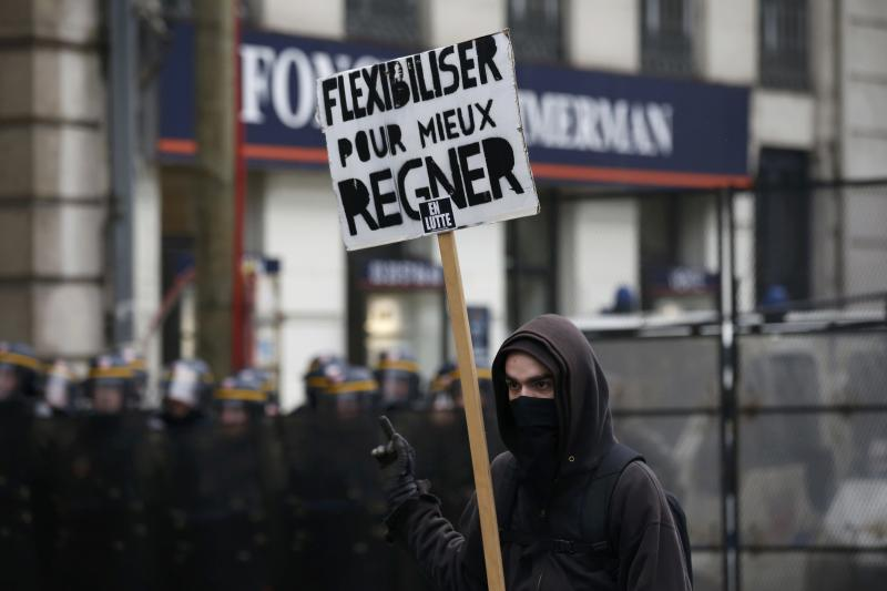 "A youth holds a placard which reads ""flexibility to better rule"" as he stands near French CRS riot police during a demonstration against the French labour law proposal in Lille"