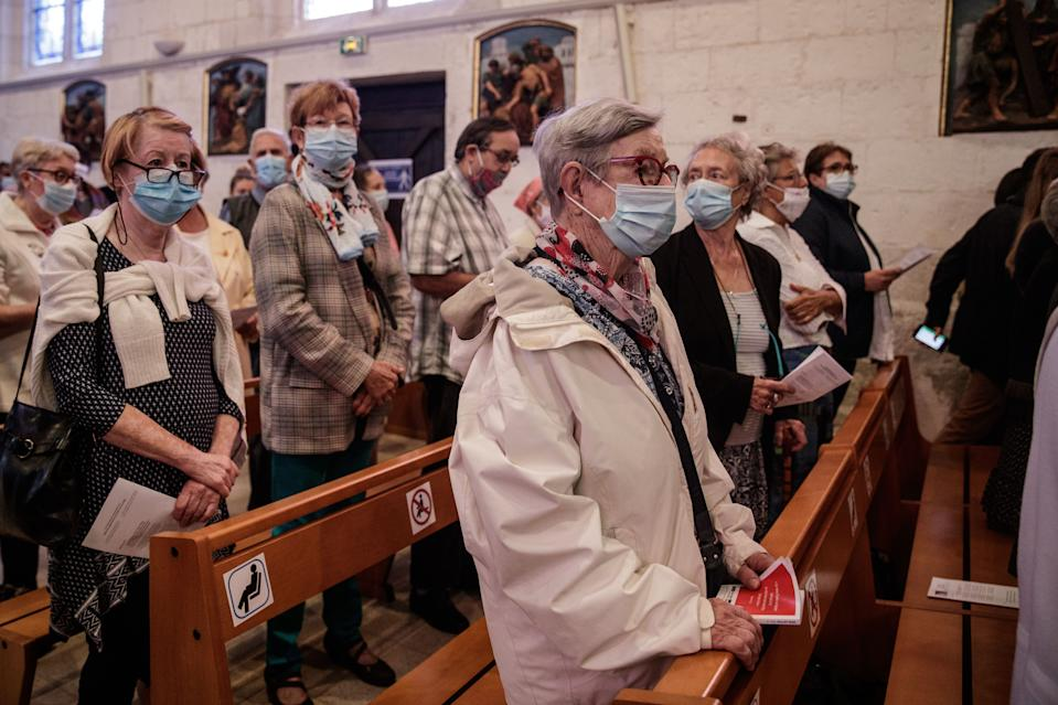 Catholic worshippers wear face masks as they attend a mass in the Church of Saint-Etienne in the city of Saint-Etienne-du-Rouvray in France. (Sameer Al-Doumy/AFP via Getty Images)