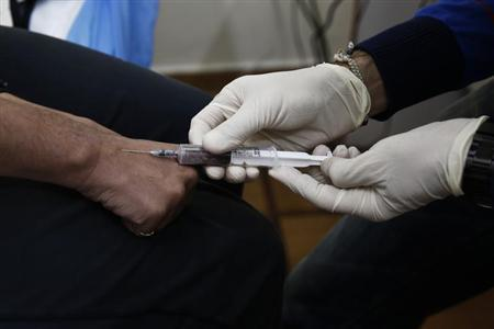 A drug user gives blood sample for a HIV test inside a clinic in Athens