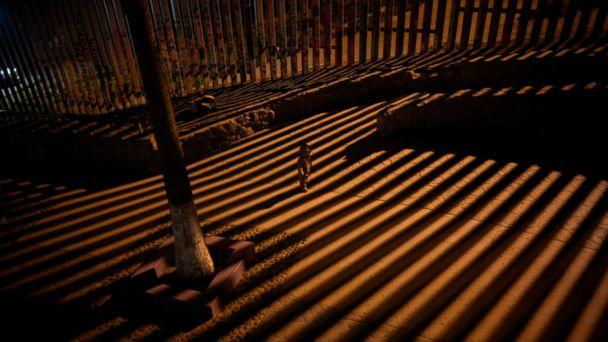 PHOTO: In this Jan. 11, 2019 photo, a boy plays as floodlights from the United States filter through the border wall in Tijuana, Mexico. (AP)
