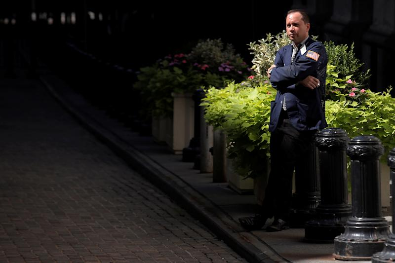 A trader stands outside the New York Stock Exchange.