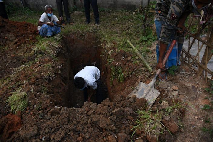 A worker digging a cemetery in Guwahati,  India.