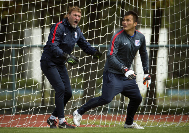 In this Thursday, April 9, 2015 photo, Spanish coach Juan Mesquida Garcia, left, shouts instructions to Shanghai Shenhua goalkeeper Qiu Shengjiong as they practice at the team's training facility in Shanghai. While a few years ago Chinese Super League (CSL) soccer was mired in corruption scandals and poor play, Shenhua is emblematic of the new and improved CSL - it's increasingly globalized, brimming with newfound professionalism and flush with cash. (AP Photo/Mark Schiefelbein)